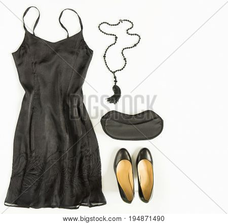 Cocktail dress outfit night out look on white background. Little black dress evening bag black shoes black tassel necklace. Flat lay top view
