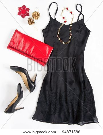 Christmas party outfi. Cocktail dress outfit night out look on white background. Little black dress red evening clutch black shoes red ang gold necklace. Flat lay top view