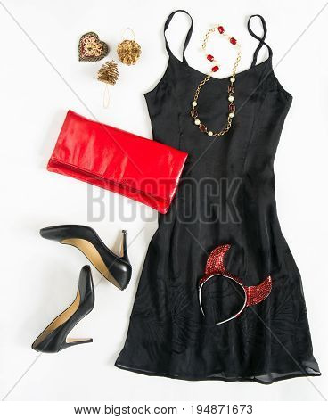 Christmas party outfit. Cocktail dress outfit night out look on white background. Little black dress red clutch black shoes red ang gold necklace and carnaval devil horns. Flat lay top view