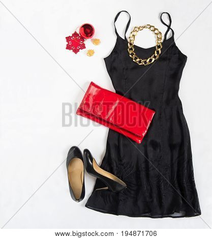 Christmas party outfit. Cocktail dress outfit night out look on white background. Little black dress red evening clutch black shoes red ang gold necklace. Flat lay top view
