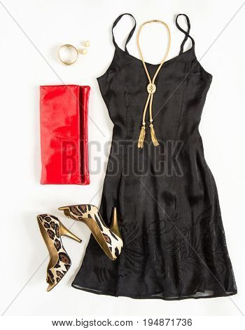 Christmas party outfit. Cocktail dress outfit night out look on white background. Little black dress red clutch leopard shoes gold necklace. Flat lay top view