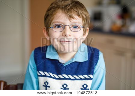 Portrait of little cute school kid boy with glasses and colorful school uniform fashion clothes. Child smiling and looking at the camera. Boy with missing front teeth