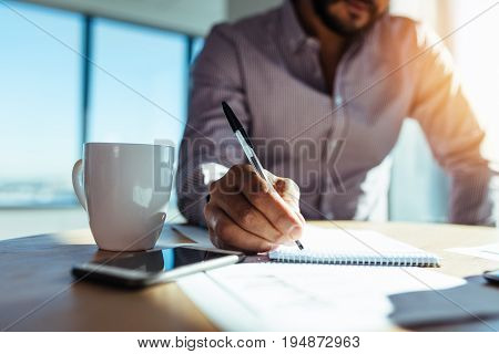 Business investor writing in notepad with a coffee cup on the desk. Closeup of a businessman's hand holding pen and making notes.