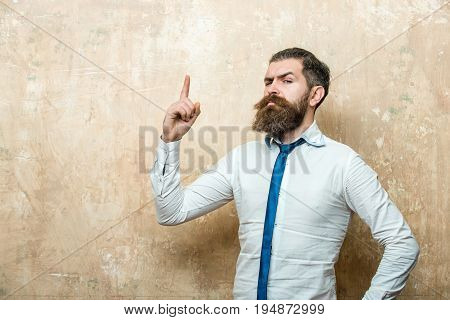 bearded man or hipster with long beard and stylish hair on serious face in tie and white shirt on textured beige background with raised finger