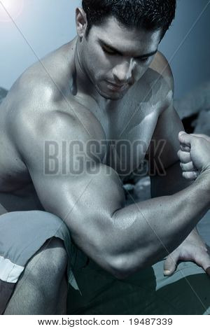 body builder flexing his arm with blue treatment