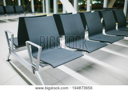 Empty waiting area of the airport with seats in a row at night. Night flight, transfer, waiting at the airport.