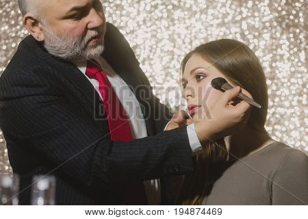 makeup. Professional visagiste man or bearded artist in business suit applying powder on cute girl or pretty woman face skin with brush. Fashionable model with long hair in beauty salon. Visage