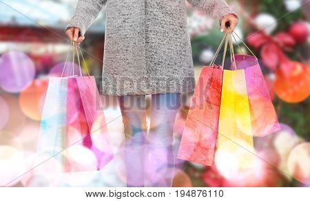 Young woman with Christmas purchases on blurred background