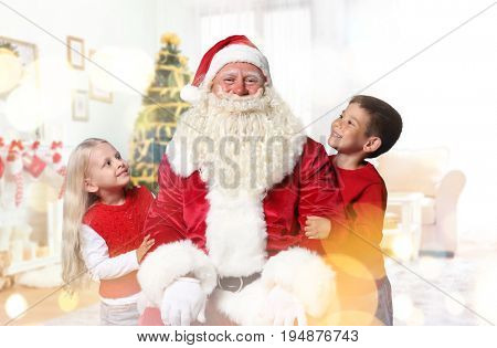 Authentic Santa Claus with little children at home. Christmas and New Year celebration