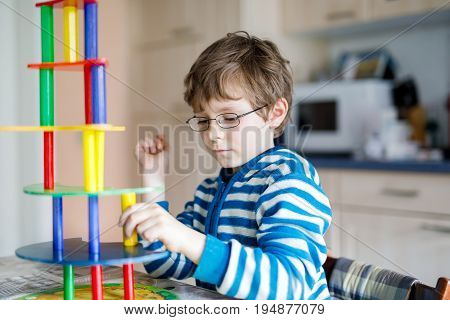 Blond child with glasses playing with lots of colorful wooden blocks game indoor. Active funny kid boy having fun with building and creating, balance toy. Home, kidsroom. Cognitive development