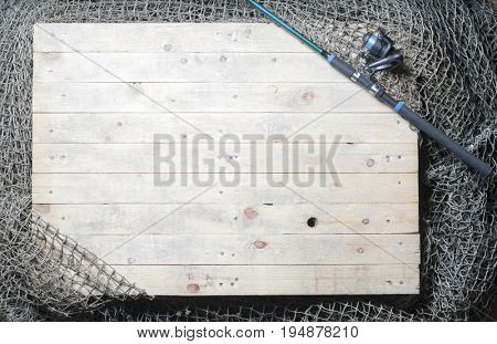 Fishing nets and spinning rod over the wooden background. Still-life and objects.