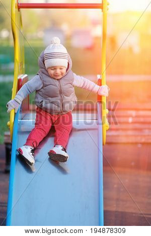 Portrait of toddler child wearing vest jacket outdoors. One year old baby boy at playground slide