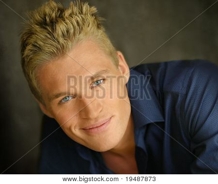 Close up portrait of a young happy blond man