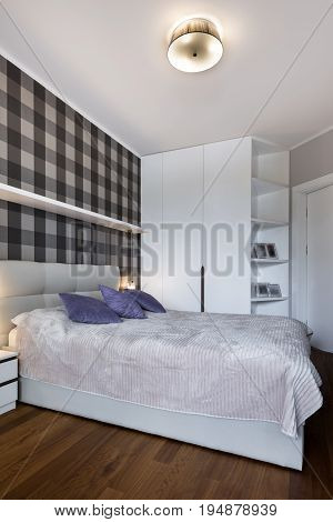 Modern bedroom with checker pattern on the wall and wardrobe
