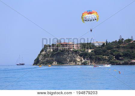 ZAKYNTHOS, GREECE - JUN 30, 2017: Motor boat tows a special parachute over blue sea near the Balcony Hotel.