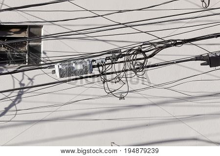 tangle of eletrical cables with shadows in street