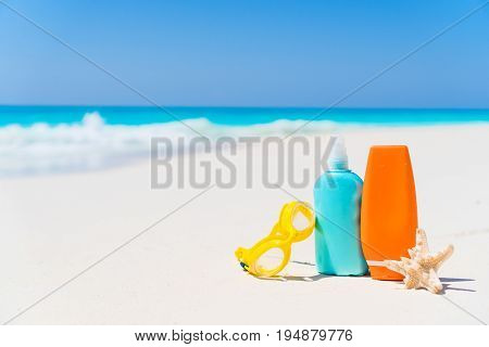 Suncream bottles, goggles, starfish on white sand background ocean