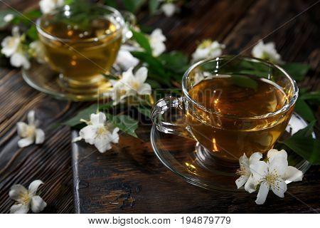 Jasmine tea with jasmine herb flower on wood background