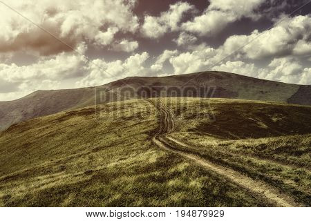 Autumn landscape. Autumn view of Carpathian Mountains , under cloudy sunset. Mountain road goes on top of the hills on sunset landscape