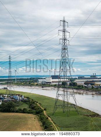 Two electrical pylons near a river bank