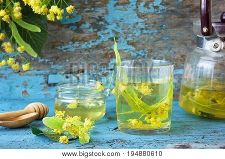 linden tea in glass on a blue background with a linden flowers and linden honey teapot. Fresh linden