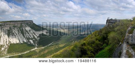 Panoramic photo of a mountain landscape. A mountain valley of a photo from top. The sky is covered with fast clouds. In the bottom of gorge a road.