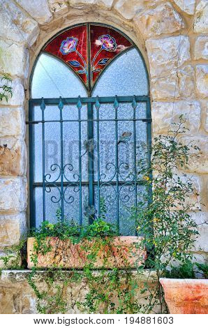 A window with a stained-glass window miraculously preserved in a small village