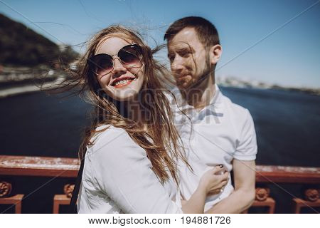 Happy Woman With Windy Hair In Sunglasses Smiling, Stylish Couple In Love Having Fun On Bridge In Th