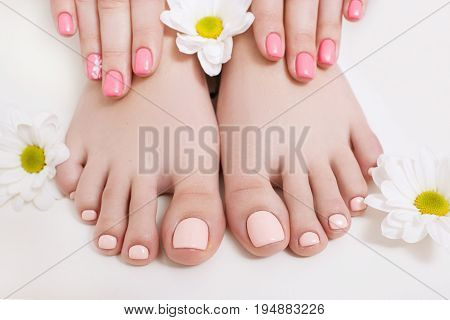 Nude pedicure and manicure for spring. Woman hands and feet on white background closeup. Result of spa salon procedure