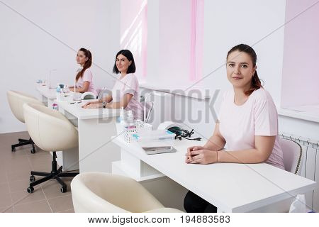 Beautician team in salon interior. Three women sits at manicure workplace