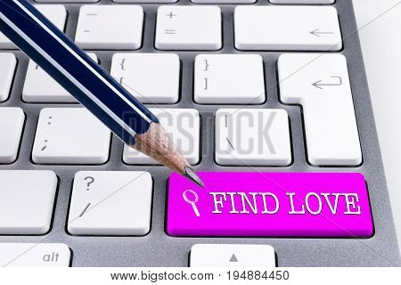 Close up view of a Computer notebook keyboard with office pencil and one pink button FIND LOVE technology background empty space for text