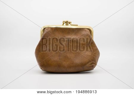 Brown leather purse isolated on white background. Old fashion wallet with antique metal edge.