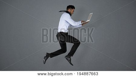 Businessman using laptop while jumping against grey background