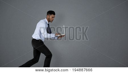 Businessman using laptop while running  against grey background