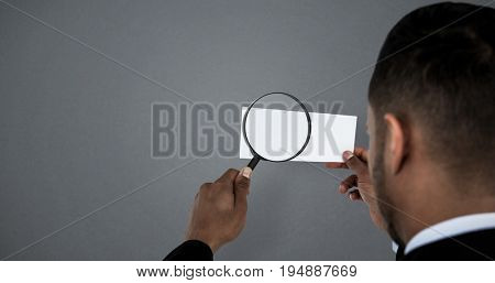 Rear view of man holding magnifying glass on paper against grey background