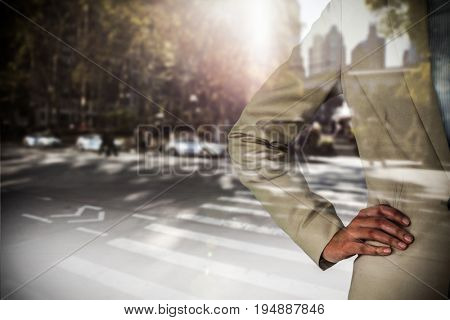 Mid section of businesswoman with hand on hip against picture of a city