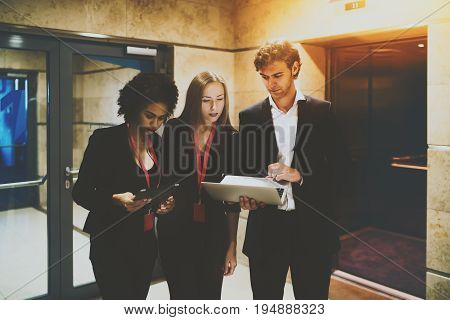 Man in formal suit sharing to his both female colleagues (young afro american probationer with digital pad and attractive caucasian woman) new presentation before business meeting via modern laptop