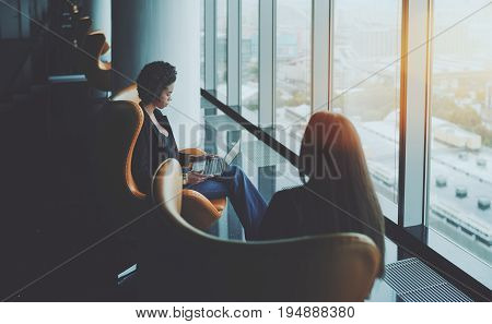 Two ladies sitting on armchairs of luxury office with multiple reflections in skyscraper near window: biracial woman working on modern laptop and her colleague viewed from back with long hair