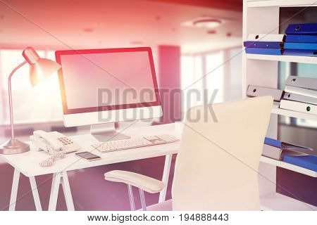 Computer with telephone and mobile phone at desk against empty chairs and table in boardroom