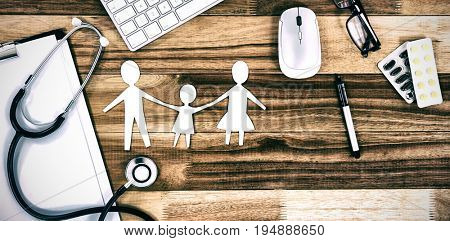 Paper cut out family chain with various medical equipment and keyboard on table
