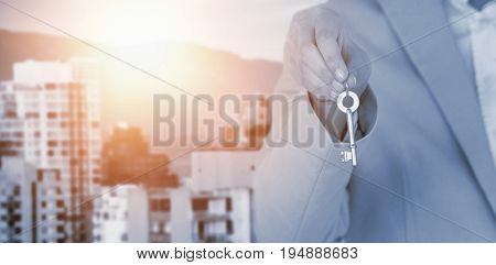 Mid section of executive showing new house key against buildings against mountain