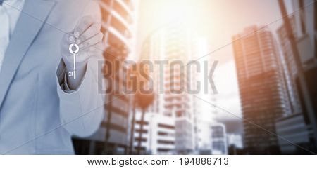 Mid section of female executive showing new house key against buildings in city