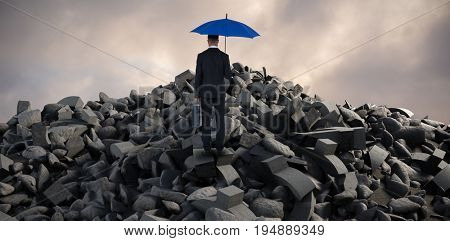 Rear view of businessman carrying blue umbrella and briefcase against full frame shot of sky