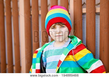 Outdoor fashion portrait of adorable little kid boy wearing colorful clothes. Spring, summer or autumn fashion for boys and children. Boy with tooth gap. Portrait of happy adorable smiling kid