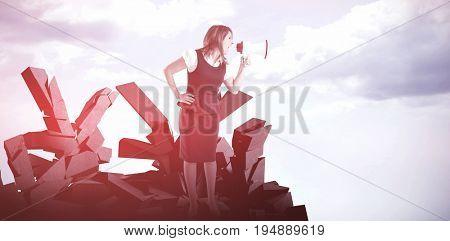 Businesswoman shouting through megaphone against blue sky