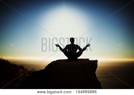 Silhouette businessman practising yoga against scenic view of mountain by sea against sky