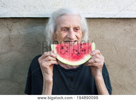 Cheerful Grandma Eating Watermelon In The Backyard
