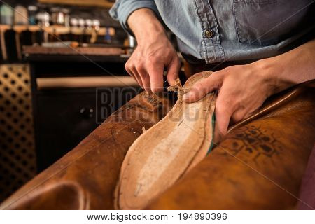 Cropped picture of shoemaker sitting in workshop making shoes