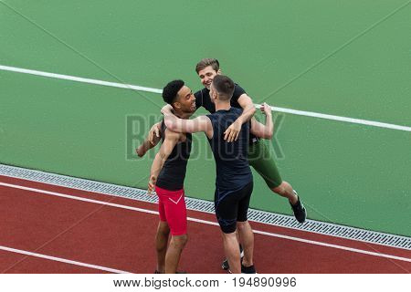 Picture of cheerful multiethnic athlete team standing on running track outdoors make winner gesture higging. Looking aside.
