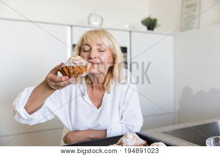 Senior woman smelling the taste of her homemade muffins while standing on a kitchen